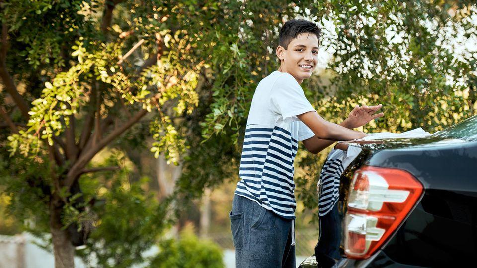 Junge putzt ein Auto