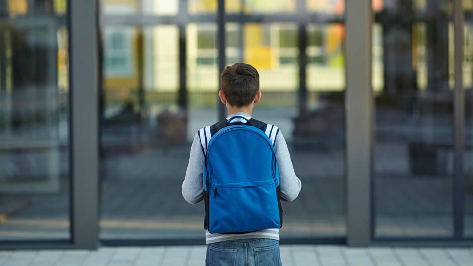 Kind mit Ranzen vor der Schule