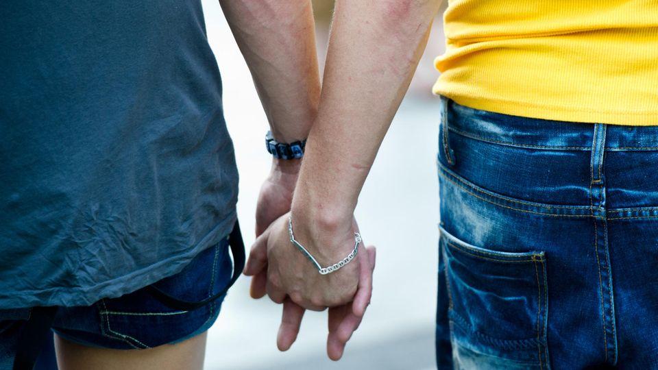 Ein schwules Paar hält Händchen.