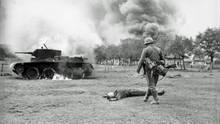 Toter Rotarmist vor seinem brennenden Panzer.