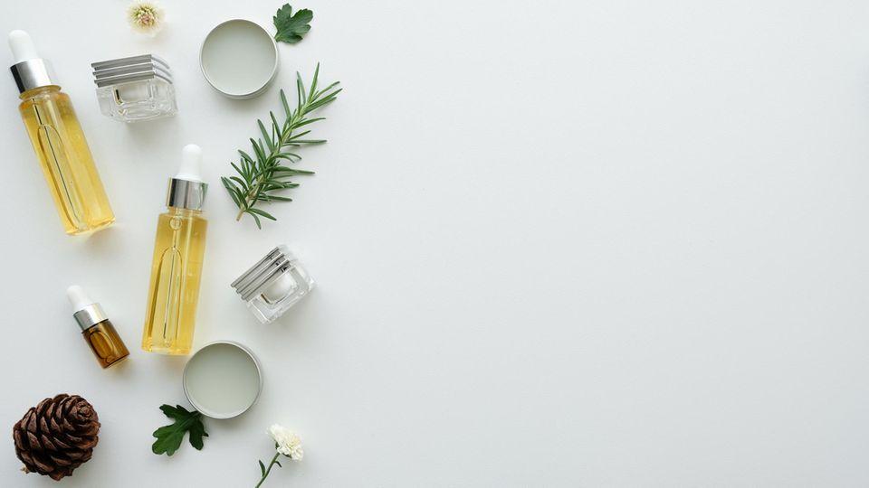 Kosmetikprodukte, Blätter, Blüten, Zweige und Tannenzapfen auf weißer Oberfläche drapiert