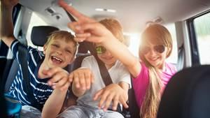 Drei Geschwister machen Quatsch auf der Rückbank im Auto