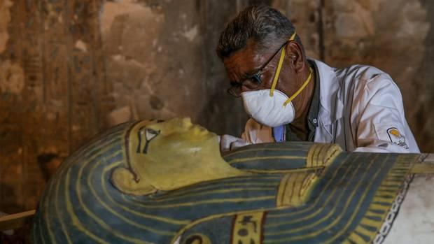 Ein Archäologe begutachtet einen alten Sarkophag