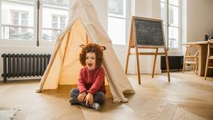 Ein Kind sitzt im Löwenkostüm vor einem Tippi