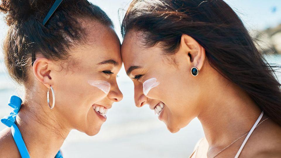 Zwei junge Frauen mit Sonnencreme auf den Wangen, stehen Stirn an Stirn und lächeln sich an