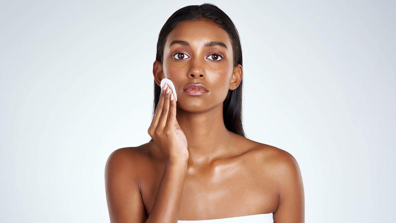 Frau trägt Gesichtstoner mit Wattepad auf