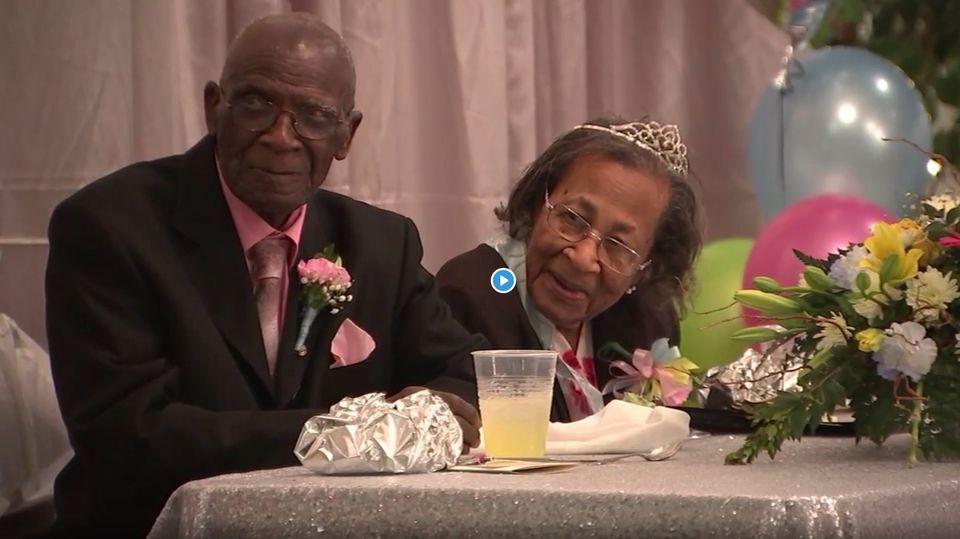 Das Ehepaar sitzt nebeneinander und lächelt, die Ehefrau trägt ein Diadem