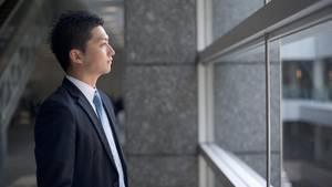 Ein Japanischer Geschäftsmann schaut aus dem Fenster