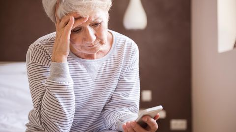 Eine alte Frau sitzt auf dem Bett uns starrt auf ihr Handy