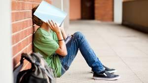 Schüler sitzt auf dem Boden und hält ein Schulheft über sein Gesicht.