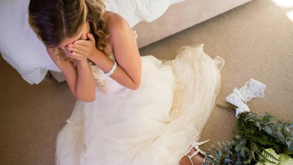 Braut sitzt neben dem Bett und weint