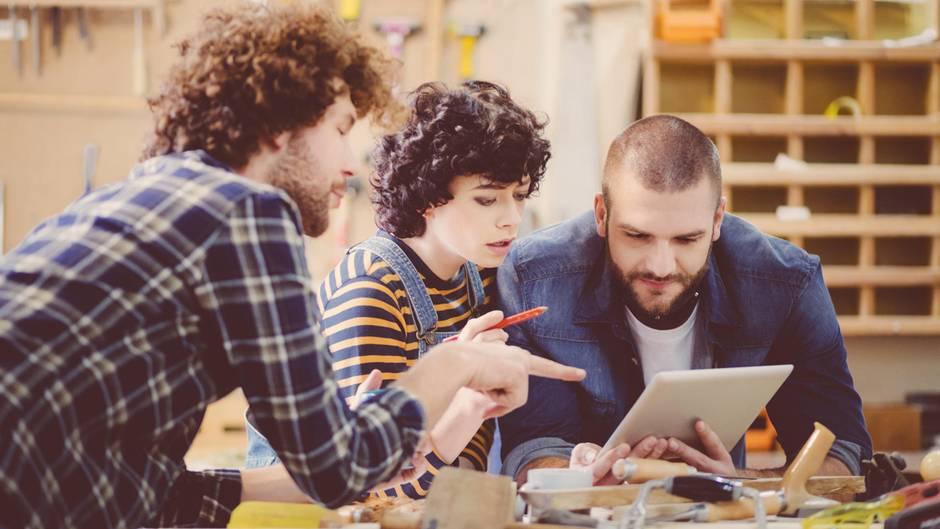 Zwei Handwerker und eine Handwerkerin besprechen etwas über Tablet gebeugt, in Werkstatt.
