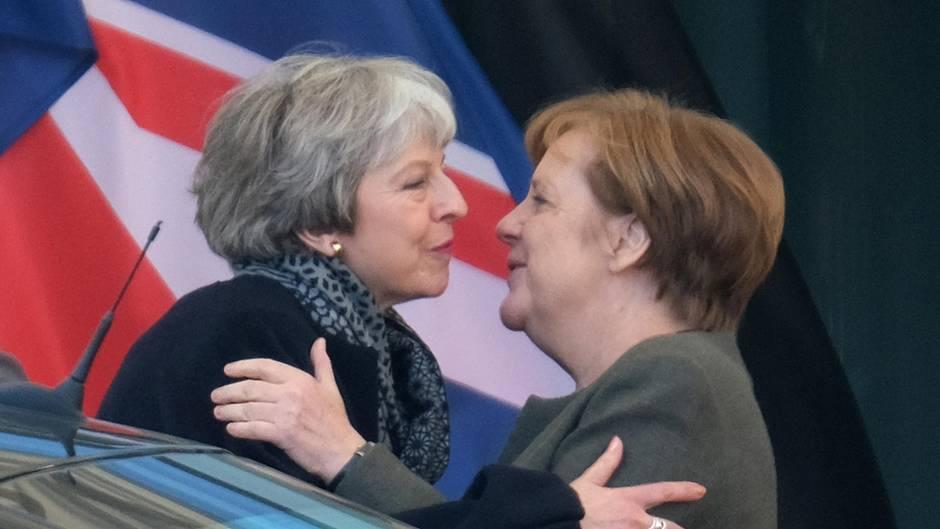 Theresa May und Angela Merkel umarmen sich zur Begrüßung vor dem Bundeskanzleramt. Davor ein Auto, dahinter der Union Jack