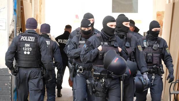 Ein Trupp voll vermummter Bundespolizisten verlässt nach eine Razzia ein Grundstück