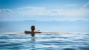 Frau in einem Infinity Pool schaut in die Ferne