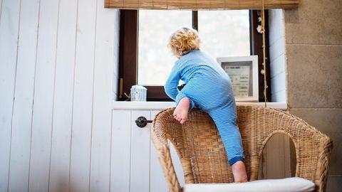 Ein Kleinkind klettert von eine Stuhl auf eine Fensterbank