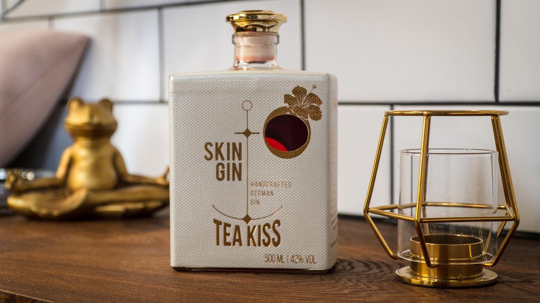 """Skin Gin - Edition Tea Kiss  Dieser Gin ist ein echtes Nordlicht und wird im """"Alten Land"""" nahe Hamburg destilliert. Optisch gibt es fast keine schönere Gin-Sorte. Das Besondere: In der Manufaktur wird jedes Botanical gesondert destilliert, bei den meisten Gins werden alle Botanicals gleichzeitig destilliert. Skin Gin wird auf Basis von Weizenalkohol hergestellt. Jede einzelne Flasche wird von Hand in einer Manufaktur in Nordbayern mit einer Kupferfolie umwickelt und heiß geprägt.    Wie schmeckt er?Wäre der Tea Kiss Gin ein Mensch, man würde bei Tinder sofort nach rechts swipen. Doch nach dem ersten gemeinsamen Abend würde man hoffen, dass man sich nie mehr wiedersieht. Er ist quasi der One-Night-Stand unter den Spirituosen. Zu süß, blumig, mit Tendenzen zum aufgelösten Gummibärchen. Die Minze im Abgang erinnert an Pfeffi, was leider nicht als Lob zu verstehen ist. Wer seine Drinks süß mag, könnte jedoch Gefallen daran finden. Der Gin istabsolut Geschmackssache. Ein weiteres Manko: Die rote Farbe ist künstlich und kommt vom zugesetzten Farbstoff.    Wie sollte man ihn trinken?Am besten pur auf Eis oder mit einem sehr dezenten Tonic Water.    Preis: etwa 39 Euro (0,5 Liter)"""