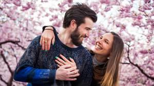 Frühlingsgefühle: Ein junges Paar vor einem blühenden Kirschbaum