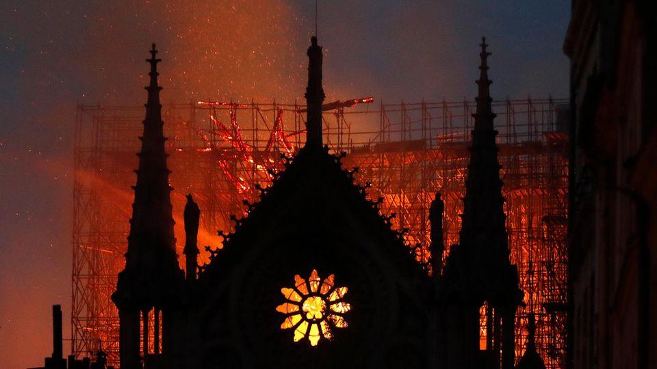 Hinter dem Giebel von Notre Dame mit seinem typischen Rosetten-Fenster erhellt Feuerschein den Himmel über Paris