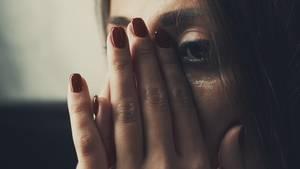 Nahaufnahme vom Gesicht einer Frau, die sich mit flacher Hand Tränen vom Gesicht wischt.