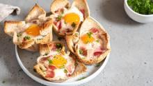 5. Unkomplizierte Eiergerichte  Kein Brunch ohne Ei. Sie können sie gekocht, als Rühr- oder Spiegelei, als Omelette oder Frittata servieren, allerdings bedeutet das oft auch, dass Sie als Gastgeber viel Zeit am Herd verbringen müssen, denn ein Rührei, Omelett oder Spiegelei schmeckt am besten frisch zubereitet. Unser Vorschlag lässt sich gut vorbereiten und variieren - und Sie können als Gastgeber entspannt mit am Tisch sitzen:      Deftige Eier-Muffins Die Vertiefungen eines Muffinblechs einfetten. In einer Pfanne einige Scheiben Bacon anbraten (für jenen Muffin eine), währenddessen ein paar Scheiben Scheiben (Vollkorn-)-Toast leicht rösten. Mit einem schmalen Glas oder Dessertring (in der Größe des Muffinbodens) Böden aus dem Brot ausstechen und je einen Boden in die Vertiefung legen. Den noch heißen Speck wie einen Ring in die Mulde legen. Er bildet den Rand. In jede Vertiefung ein Ei schlagen, mit etwas Salz würzen und im heißen Ofen 12 bis 15 Minuten backen, je nachdem, wie weich das Ei noch sein soll. Herausholen, kurz abkühlen lassen, mit Pfeffer und vielleicht noch Schnittlauch würzen und servieren. Alternativ können Sie auch je einen ganzen Toast in die Mulde drücken, dann aber vorher das Brot dünn ausrollen. Weitere alternative oder ergänzende Zutaten: frische Kräuter, Schinkenwürfel, geriebener Käse oder Gemüsestücke wie Erbsen, Tomaten, Paprika oder Zwiebeln, bei Bedarf gewürfelt.