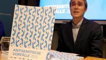 """Eine weiß-blaue gemusterte Broschüre """"Antisemitische Vorfälle 2018"""" steht auf einem Tisch. Dahinter sitzt ein Mann im Anzug"""