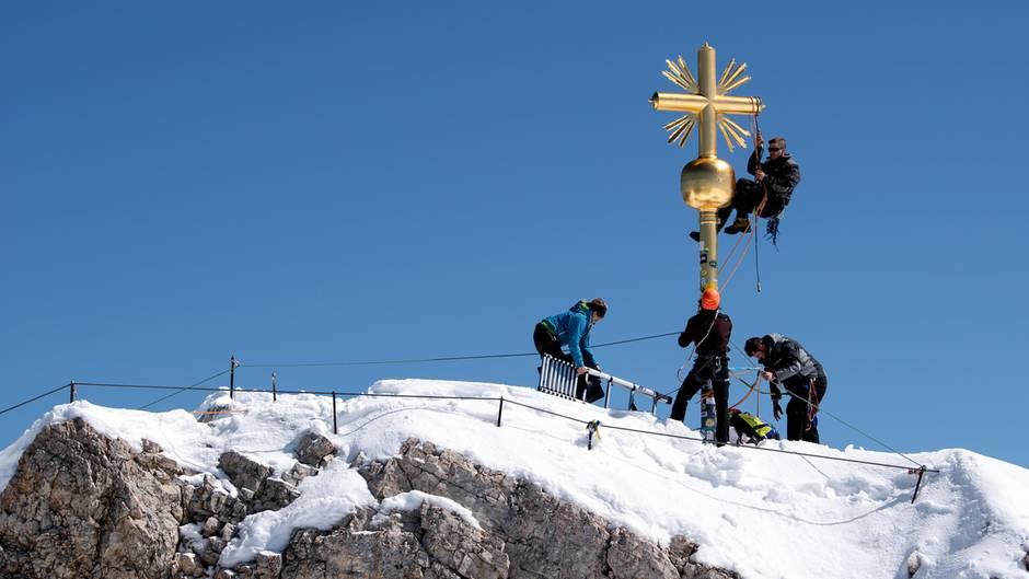Garmisch-Partenkirchen, Deutschland. In einer dreistündigen Aktion haben Schlosser das bei schweren Stürmen beschädigte Gipfelkreuz der Zugspitzerepariert. Im März war ein Stück aus dem Strahlenkranz herausgebrochen, der das vergoldete Kreuz am höchsten Berg Deutschlands (2962 Meter) schmückt.