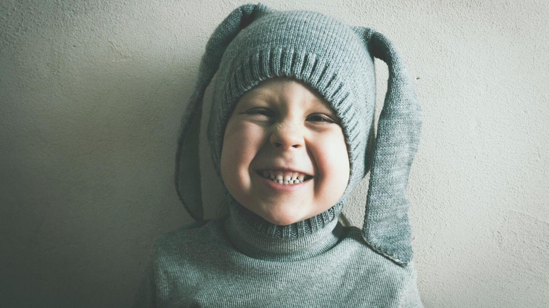 Ein Junge mit Strumpfhose auf dem Kopf grinst verschmitzt