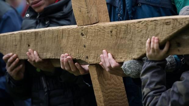 Gläubige halten bei der ökumenischen Kreuzwegprozession am Karfreitag in Lübeck ein großes Kreuz.