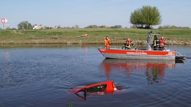 Rettungskräfte bergen ein Auto aus dem Hafenbecken in Bleckede
