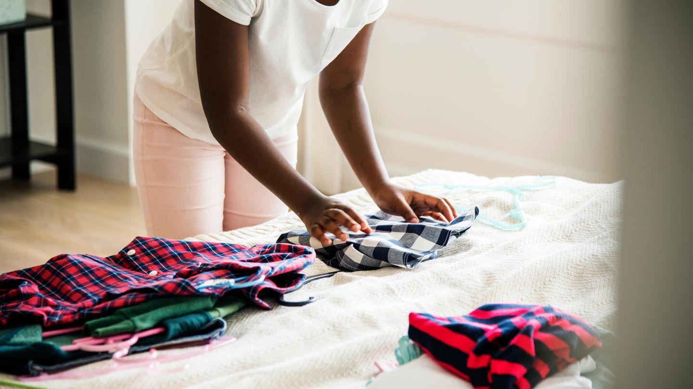 Ein Mädchen legt Wäsche zusammen
