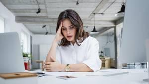 Psychische Krankheiten: Eine Frau sitzt am Schreibtisch und fasst sich an den Kopf