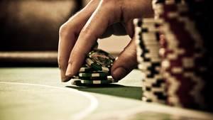 Eine Hand setzt Jetons auf einem Pokertisch als Symbolfoto für Nachrichten aus Deutschland