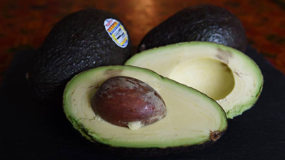 Eine aufgeschnittene Avocado liegt vor zwei weiteren Avocados