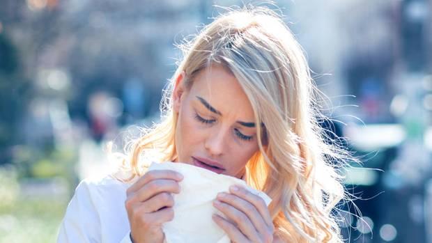 Pollenallergie und Heuschnupfen: Eine Frau niest in ein Taschentuch