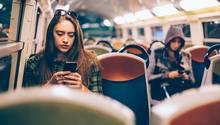Eine Frau sitzt in der U-Bahn und schaut auf ihr Handy