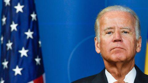 Joe Biden steht vor blaume Hintergrund und neben einer US-Flagge und richtet sich mit der rechten Hand die Krawatte