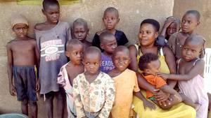 Die Uganderin Mariam Nabatanzi sitztin Kasawomit zwölf ihrer Kinder vor dem Haus, auf ihrem Schoss sitzt das jüngste Mädchen Sudaisha.
