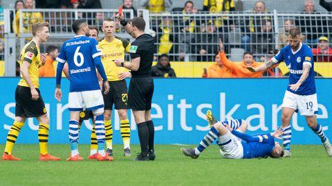 Schiedsrichter Felix Zwayer (m.)zeigt Dortmunds Marco Reus (l.) die rote Karte