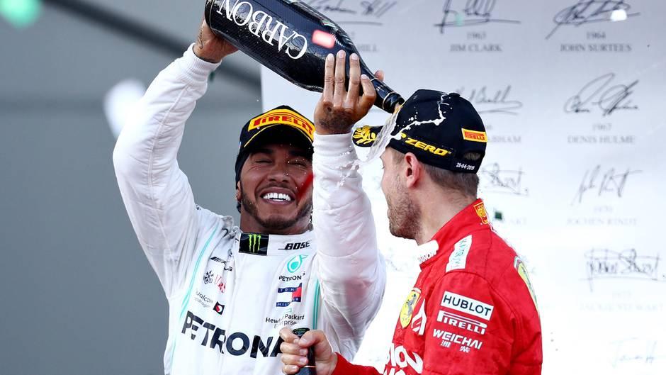 Lewis Hamilton schüttet Sebastian Vettel Schampus auf dem Podium in Bahu über den Kopf