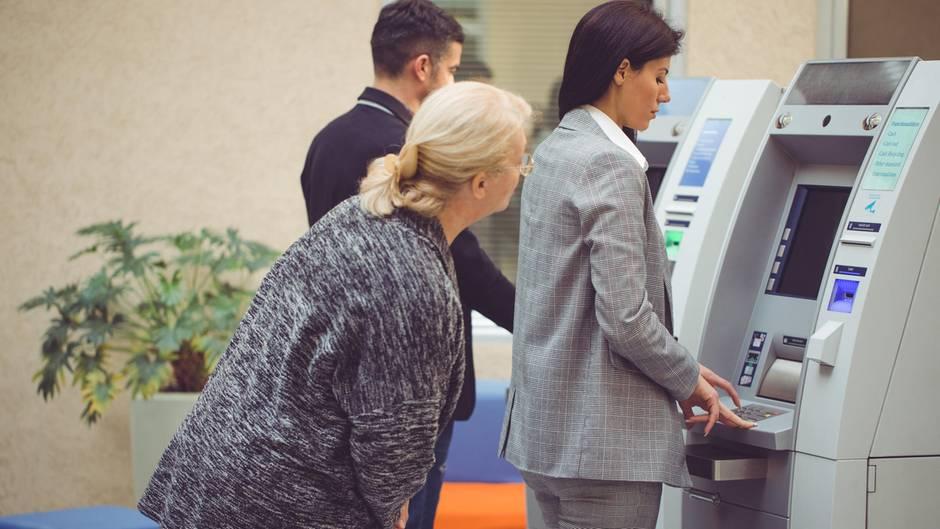 Leute stehen an am Bankautomat