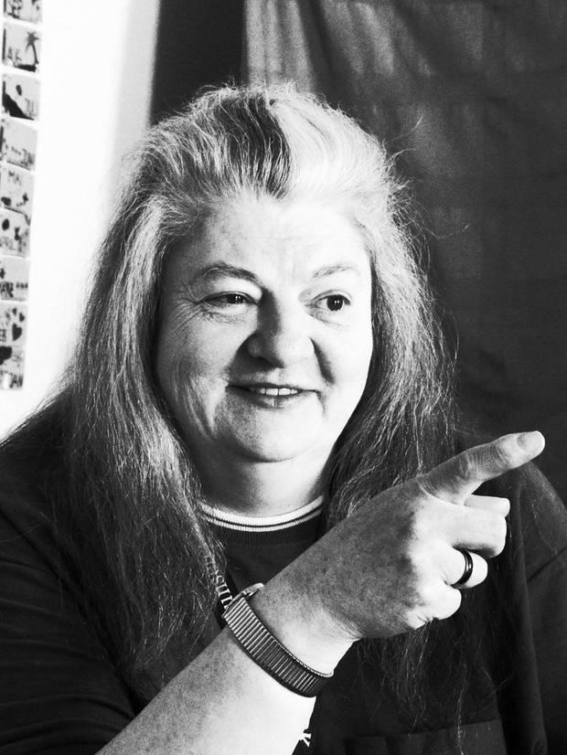 Eine grauhaarige Frau zeigt mit dem Zeigefinger und grinst