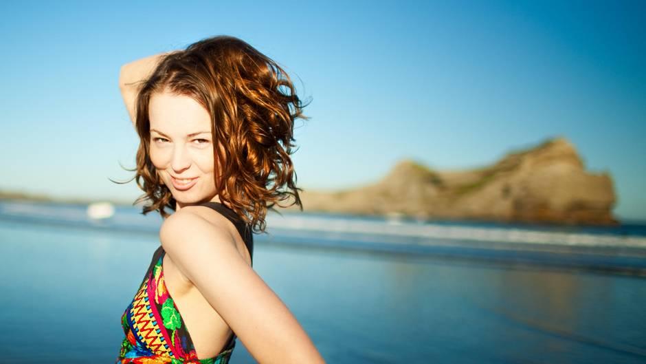 Eine hübsche Frau steht in Neuseeland am Strand