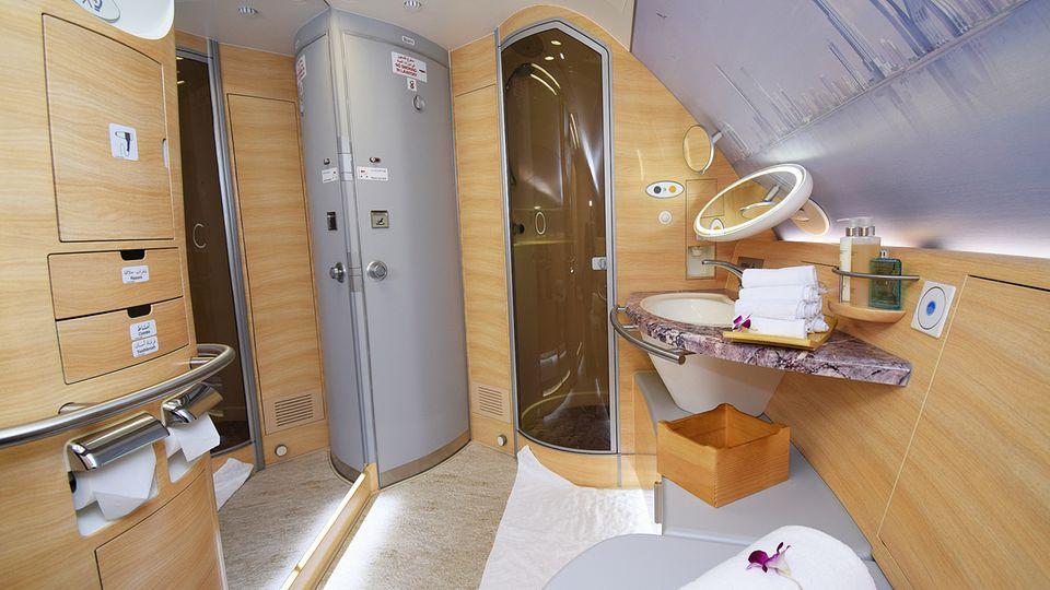 Im Airbus A380 von Emirates Airlines gibt es zwei Duschen für Passagiere der First Class. Durch einen bodentiefen Spiegel wirkt das fliegende Badezimmer noch größer. Rechts neben der Tür zur Kabine ist die gläserne Duschkabine platziert.