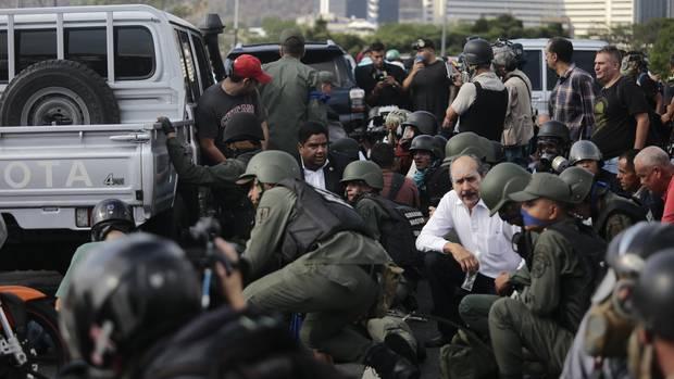 """Soldaten und Zivilisten decken sich bei einem Einsatz um die Autos, in denen der selbst ernannter Interimspräsident Guaidó nahe des Luftwaffenstützpunktes La Carlota gefahren wird. """"Als Interimspräsident von Venezuela, als rechtmäßiger Oberkommandierender der Streitkräfte, rufe ich alle Soldaten dazu auf, sich uns anzuschließen"""", sagte der Oppositionsführer auf einer Schnellstraße"""