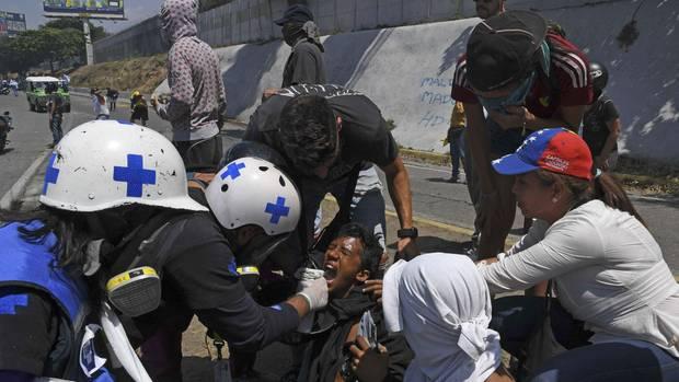 Ein oppositioneller Demonstrant wird nach dem Einsatz von Tränengas medizinisch versorgt