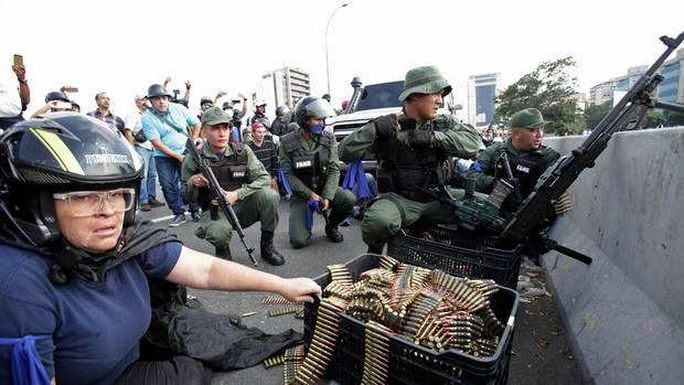 Ein Regierungsgegner sitzt mit Munition, die von bewaffneten Rebellentruppen bei einem Einsatz nahe des Luftwaffenstützpunktes La Carlota benutzt wird. Der Oppositionsführer Guaido und der inhaftierte Oppositionsführer Lopez riefen Soldaten und Bevölkerung dazu auf, gegen den Staatschef Maduro auf die Straßen zu gehen