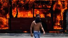 Venezuela, Caracas: Ein Demonstrant geht vor einem Bus
