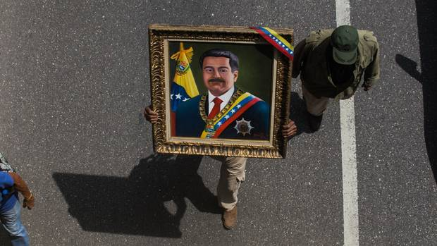 Ein Soldat in Venezuela trägt am 1. Mai ein Bild des Staatspräsidenten Nicolás Maduro