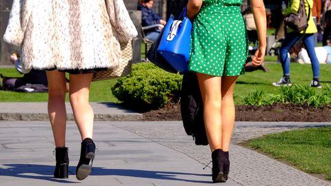 Zwei Frauen mit kurzer Hose und kurzem Rock sind von hinten zu sehen